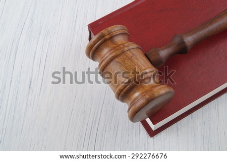 Red legal book and gavel on table with room for text - stock photo