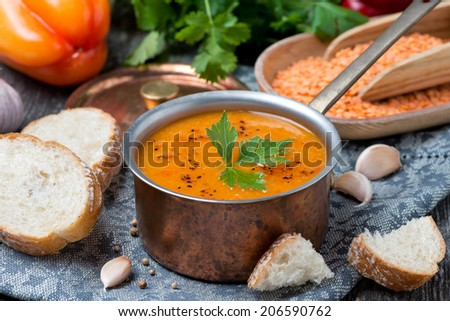 red lentil soup with pepper and spices in a copper saucepan, close-up - stock photo