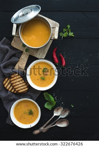 Red lentil soup with spices, herbs, bread in a rustic metal saucepan and bowls, over dark wood backdrop, top view, vertical, copy space - stock photo