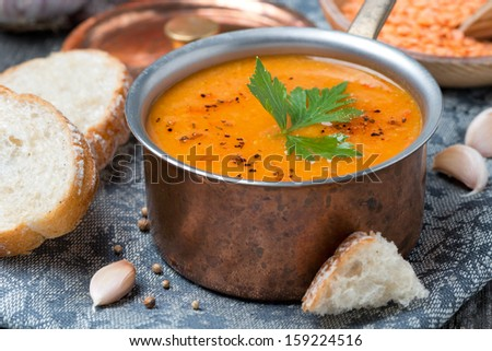 red lentil soup with spices in a copper saucepan, close up, horizontal - stock photo