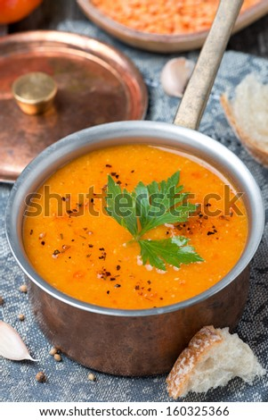 red lentil soup with spices in a copper saucepan, top view, vertical - stock photo