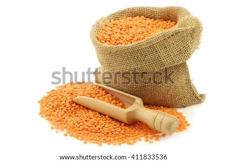 red lentils in a burlap bag with a wooden scoop on a white background - stock photo