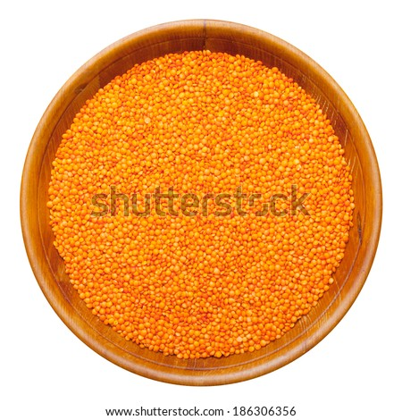 red lentils in wooden bowl, isolated