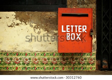 Red letterbox on tiled wall - stock photo