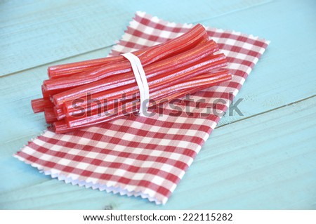 Red licorice tied with a white ribbon on a red and white checkered napkin over an old turquoise wooden table - stock photo