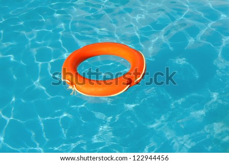 Red Life Buoy floating in swimming pool - stock photo