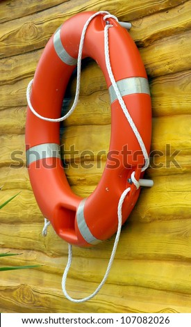red life buoy hanging on a yellow wooden wall - stock photo