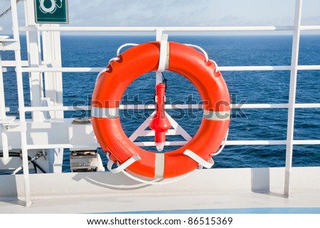 red life buoy on side of sea cruise liner - stock photo