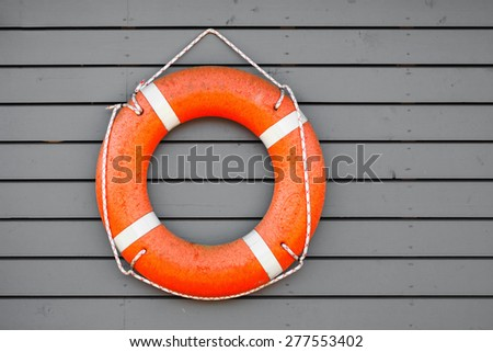 Red lifebuoy hanging on gray wooden wall of a port building - stock photo