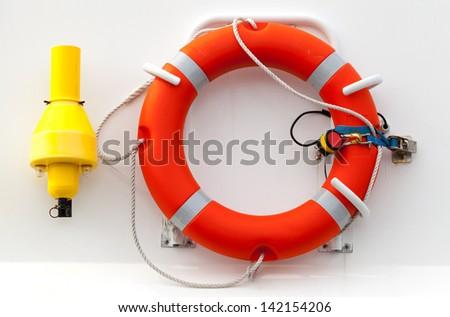 Red lifebuoy with rope on white ship wall - stock photo