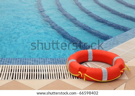 red lifebuoy with yellow ropes on tiled floor near swimming pool with stairs - stock photo