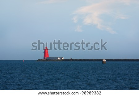 Red lighthouse and peer in a blue sea and some fluffy clouds - stock photo