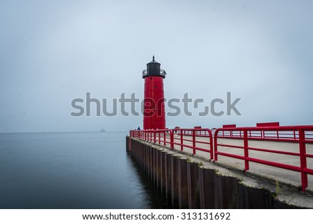 Red Lighthouse on Lake Michigan in the early morning hours of a foggy day - stock photo