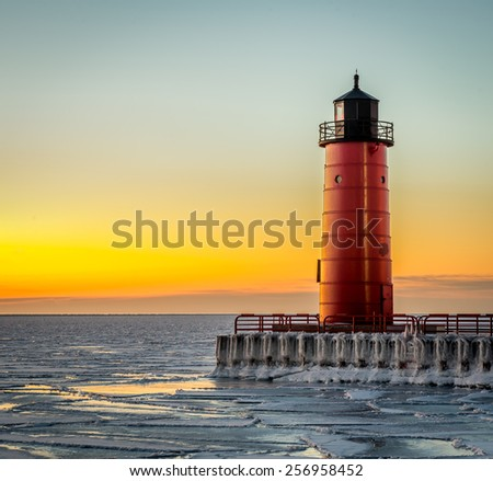 Red lighthouse on Lake Michigan shot very early in the morning at sunrise in winter. - stock photo