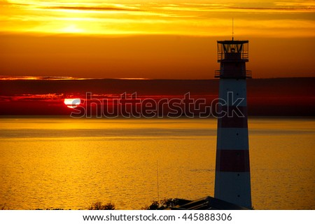 Red Lighthouse with Light Beam at Sunset.