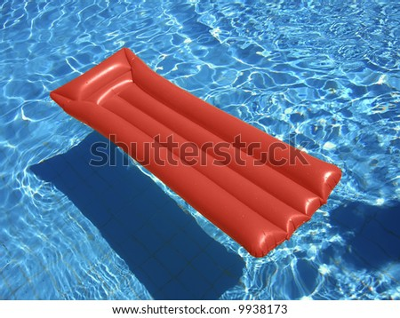 Red lilo floating on a swimming pool - stock photo
