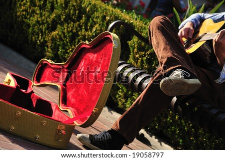 Red-lined guitar case of a street musician sitting on a bench - stock photo