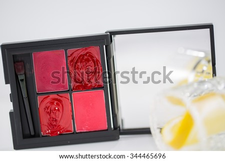 Red lipstick with golden color shoe on a white backgroud - stock photo