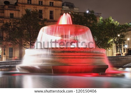 red lit fountain on Trafalgar square at night - stock photo