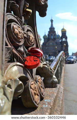Red love heart padlock on bridge over Griboedov Channel near the Church of the Savior on Blood, St. Petersburg, Russia - stock photo