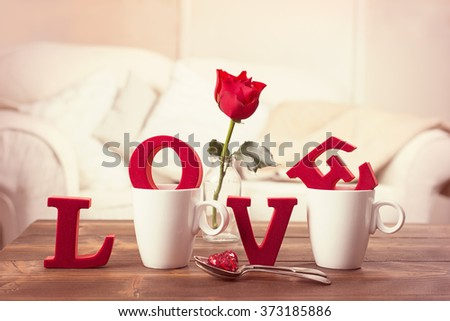 Red love letters in teacups with red rose in vase for Valentine's Day - toned to give romantic vintage feel - stock photo