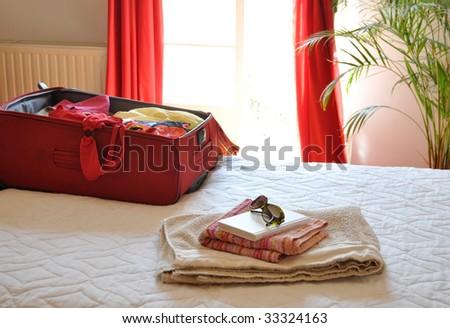 red luggage on the bed - stock photo