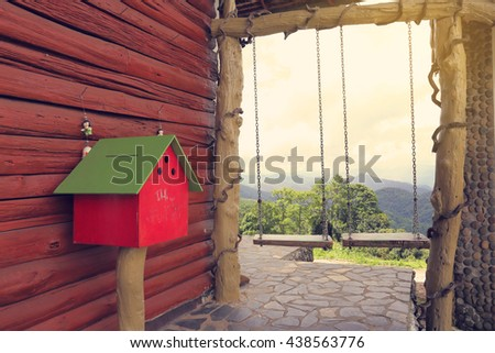 red mail box against wood wall near two swings on the hill at north of thailand - stock photo