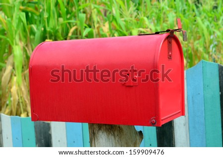 Red mail box on wooden wall - stock photo