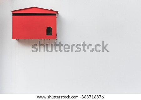 red mailbox on old white wall background