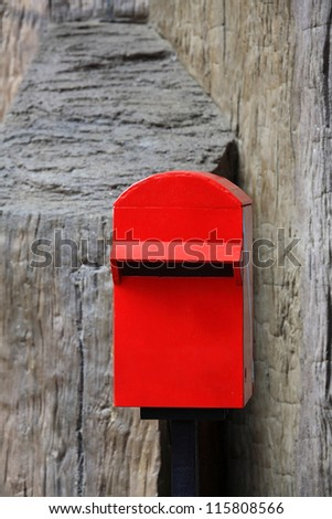 Red mailbox on rough concrete wall - stock photo