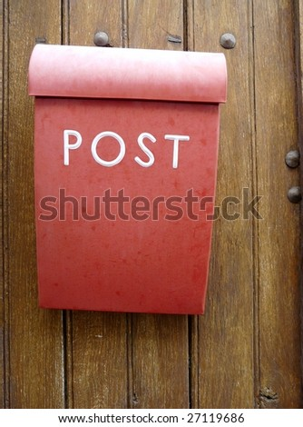 Red mailbox or postbox on a wooden door - stock photo