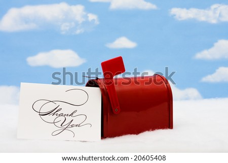 Red mailbox with white thank you card and the flag up sitting on snow with a snowflake background, mailbox - stock photo