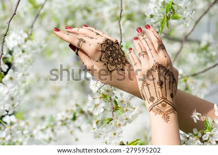 Red manicured hands with Mehndi in spring cherry blossom, Indian tradition. Horizontal composition. - stock photo