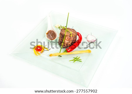 red meat with vegetables and sauce on white - stock photo