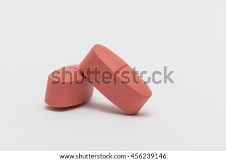 Red medicine pills heap. Isolated on white background. - stock photo