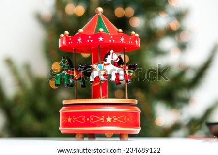Red merry-go-round horse carillon, wooden carouse, christmas decoration, Christmas tree on background - stock photo