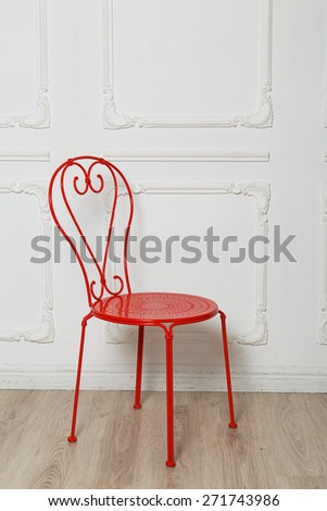 Red metal chair in a bright studio - stock photo