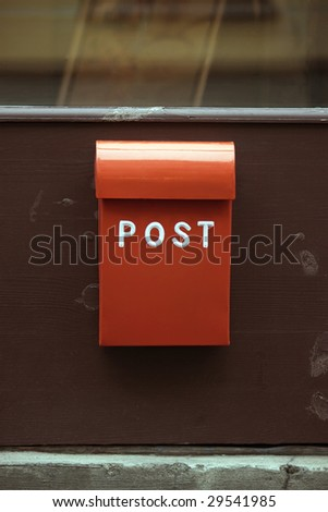 Red metal mailbox on an old wooden door - stock photo