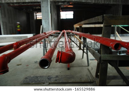 Red metal pipes on a building site lying on a rack waiting to be installed, close up view from the end - stock photo