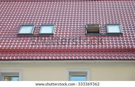 Red Metal tiled Roof with New Dormers, Roof Windows, Skylights, Rain Gutter System and Roof Protection from Snow Board - stock photo