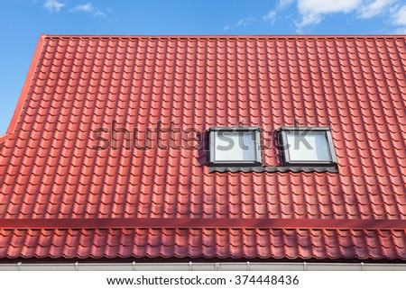 Red Metal tiled Roof with New Skylights and Roof Protection from Snow Board  - stock photo
