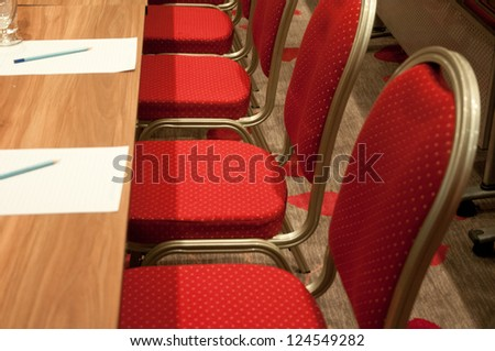 red metallic chairs of a conference room - stock photo