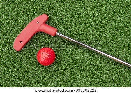 Red mini golf putter and ball laying on artificial turf - stock photo