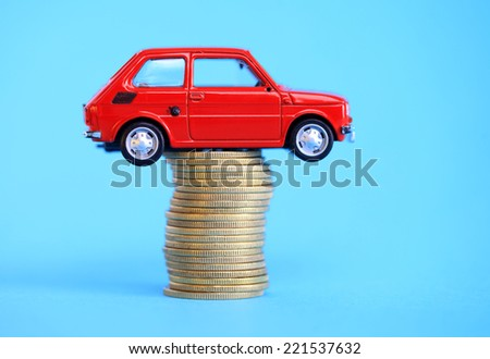 Red miniature car on coin stack - stock photo