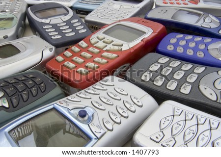 Red mobile phone handset in center of other broken old cell phones. - stock photo