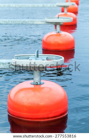 Red mooring buoys in a row floating on blue water, small European yacht club, marina port fragment, vertical photo - stock photo