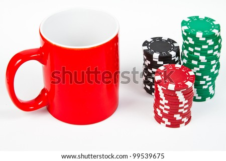 Red mug and poker chips over white background