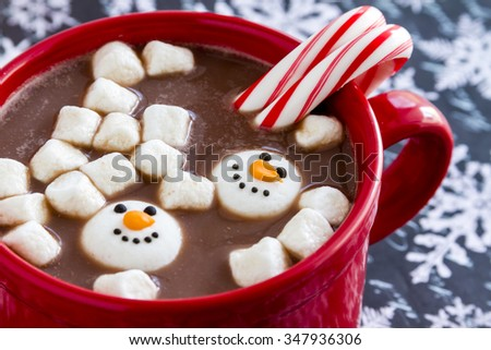 Red mug filled with hot chocolate with snowman marshmallows, peppermint candy canes on black and white snowflake background - stock photo