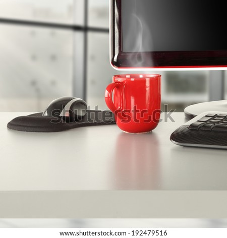 red mug of coffee and black computer  - stock photo