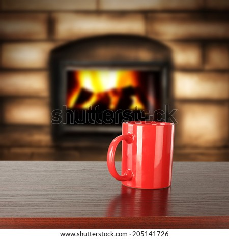 red mug of drink and fireplace  - stock photo